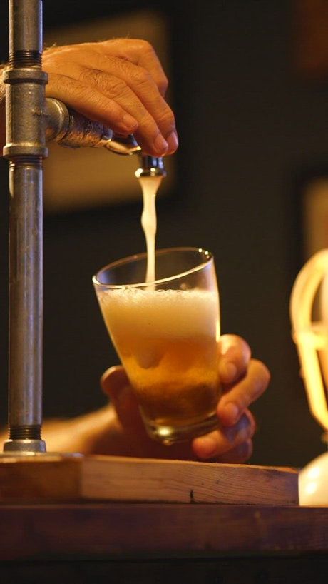 Bartender serving beer from a tap looking down at his hands