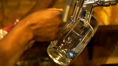 Bartender serving beer on a beer mug