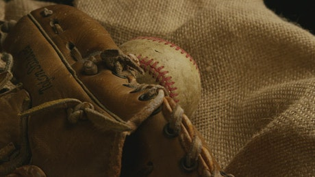 Baseball glove and a used ball over a fabric