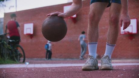 Basketball player dribbling the ball near the camera