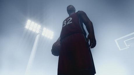 Basketball player standing under spotlights