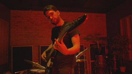 Bass player playing on a red-lit spot