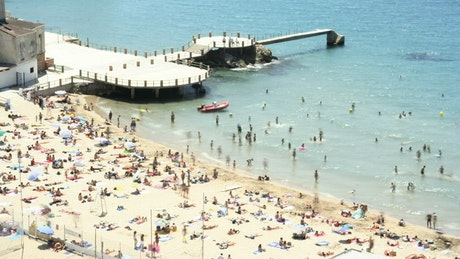 Beach full of tourists next to the pier