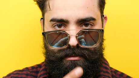 Bearded hipster man smiling with yellow background