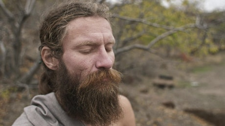 Bearded man meditates with closed eyes in nature