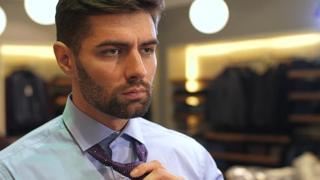 Bearded man tying a tie to his suit