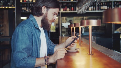Bearded man uses mobile app in urban bar
