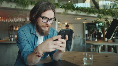 Bearded man using mobile app in airport cafe