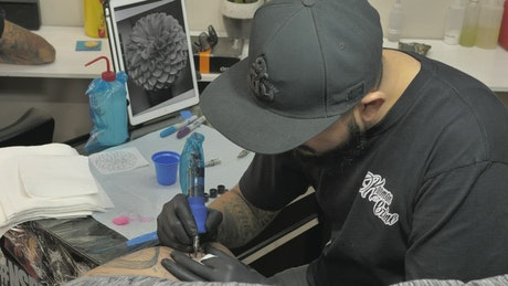 Bearded tattooist making a flower