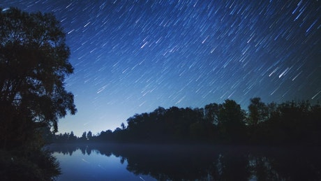 Beautiful bluish landscape of a lake and starry sky