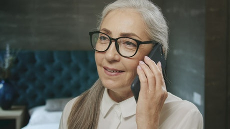 Beautiful elderly woman chats on mobile phone