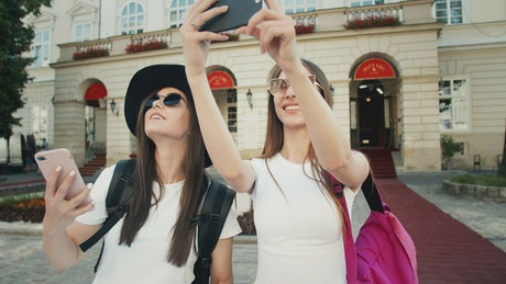 Beautiful tourists pose for social media in European town