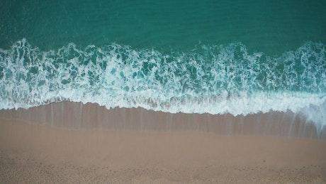 Beautiful waves breaking on golden sand