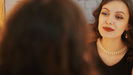 Beautiful woman applies red lipstick in mirror