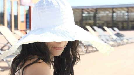 Beautiful woman in sun hat looks up andsmiles