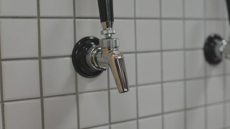 Beer being served from a tap on a wall