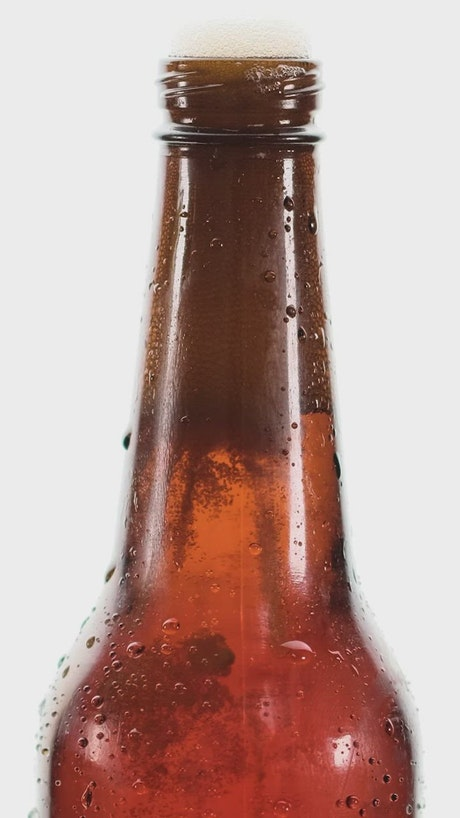 Beer bottle spilling foam on a white background