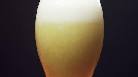 Beer foam settling in a glass