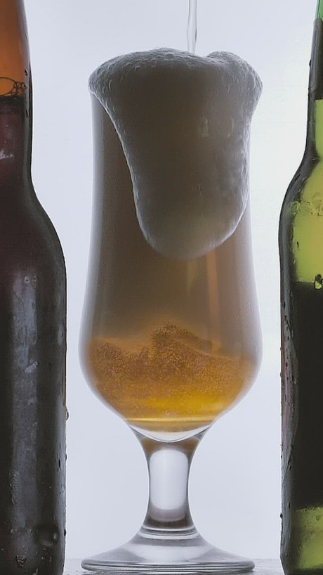 Beer foam spilling into a glass on white background