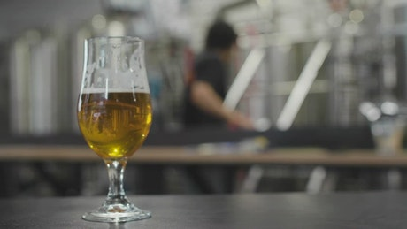 Beer glass with factory in the background