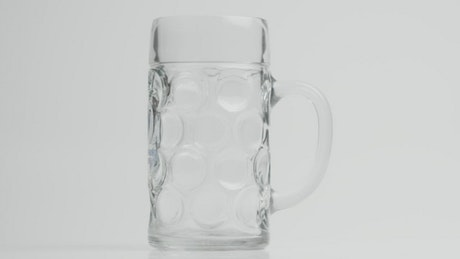Beer pouring in slow motion into a mug beer
