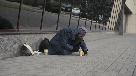 Beggar picking change from the street