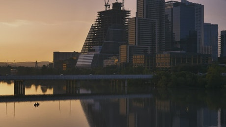 Big city of tall buildings at sunset from a lake