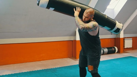 Big man doing heavy exercise in a gym