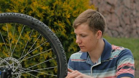 Bike repair man spins wheel and gives OK
