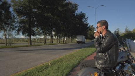 Biker resting next to a highway