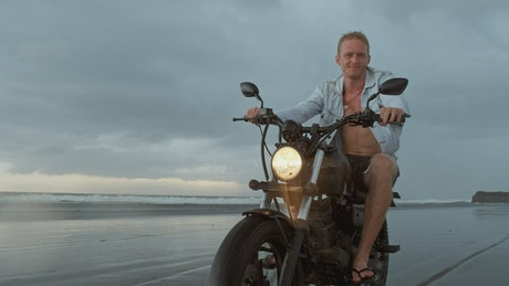 Biker riding his motorcycle on the beach