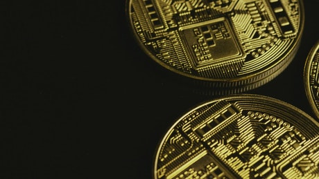 Bitcoins coins rotating slow on a black surface