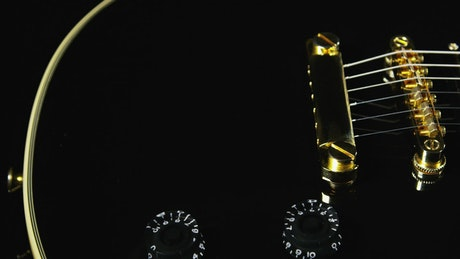 Black guitar with golden strings