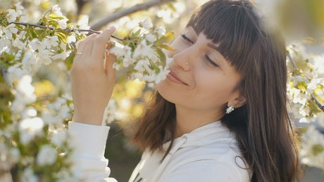 Black haired woman smelling white flowers
