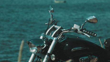 Black motorbike by a lake