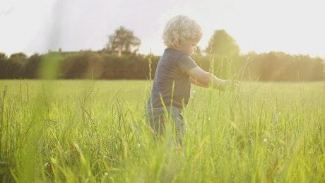 Blonde boy playing in a field