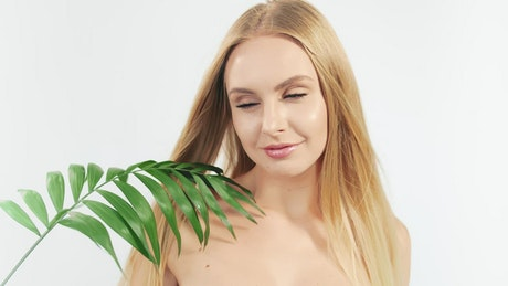 Blonde woman and a green fern on a white background.