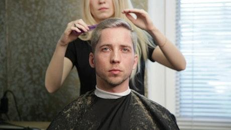 Blonde woman cutting hair