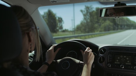 Blonde woman driving on road