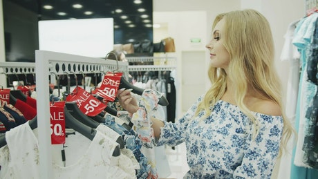 Blonde woman holds up dress in shopping mall
