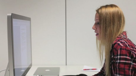 Blonde woman in front of a computer