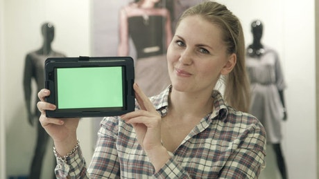 Blonde woman showing a tablet with a green screen