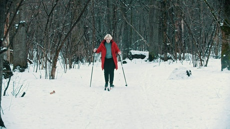 Blonde woman skiing in the forest