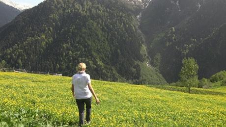 Blonde woman walking in a flower field in the mountain