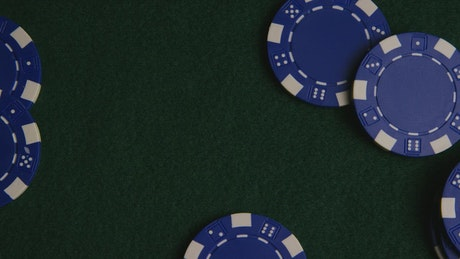 Blue casino chips on a green surface