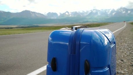 Blue luggage sits on the side of a mountain road