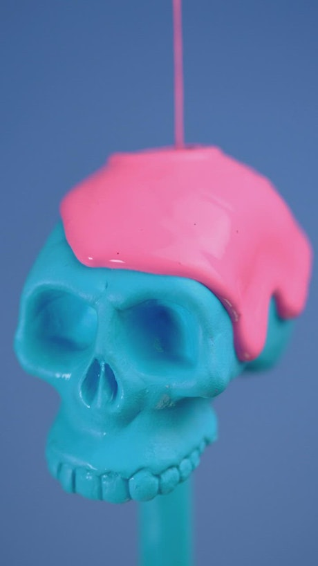 Blue plastic skull covered with a pink liquid on a blue background