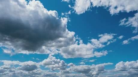 Blue sky with moving white clouds