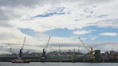 Boat sailing past cranes