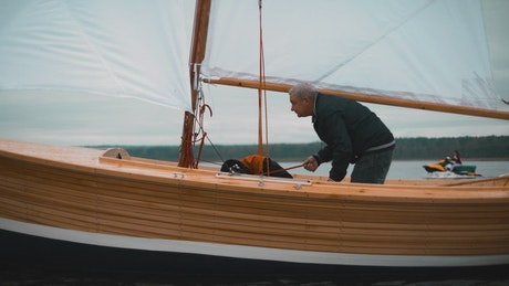 Boaters repairing a wooden sailboat